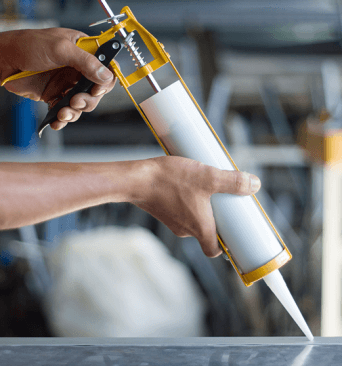 A man using caulk during home renovation job