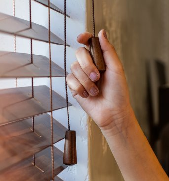 Womans hand pulls string on wooden blinds