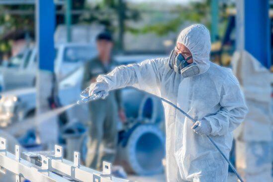 Worker using an airless sprayer
