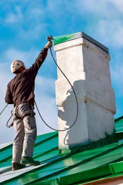 Worker painting chimney green with Tritech airless sprayer