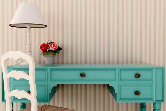 Striped wallpaper in front of turquoise writing desk